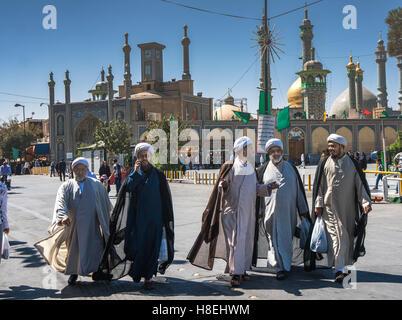 Chatting mullahs against the minarets of the Hazrat-e Masumeh (Holy Shrine), Qom, Iran, Middle East - Stock Photo