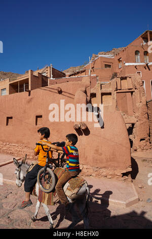 Boy with donkey gives bicyclist a lift in 1500 year old traditional village of red mud brick houses, Abyaneh, Iran, - Stock Photo