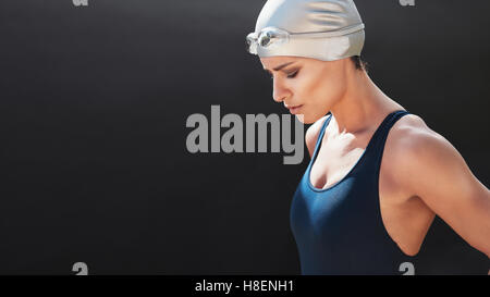 Portrait of young female swimmer concentrating on black background. Young woman in swimsuit with copy space. - Stock Photo