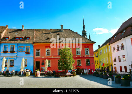 People at restaurant in Old Town of Sighisoara. Clock Tower on the background. Romania