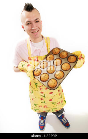 Man with Mohawk  holding muffin tin - Stock Photo