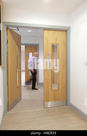 fire doors in a new London office building showing ironmongery, signs and  blurred man passing - Stock Photo