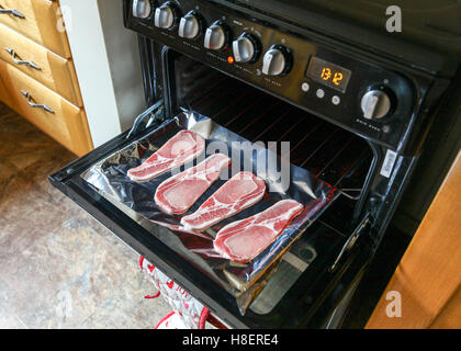 Rashers of bacon on a grill pan on an oven - Stock Photo