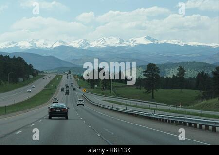 Driving on the Highway, Rocky Mountains in the Distance - Stock Photo