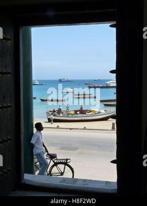 View of fishermen working on their boat in port of Stone Town, Zanzibar, seen through an ancient wooden door with - Stock Photo