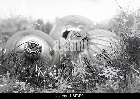Silver Christmas or New Years balls on silver sparkle background with snowflakes - Stock Photo