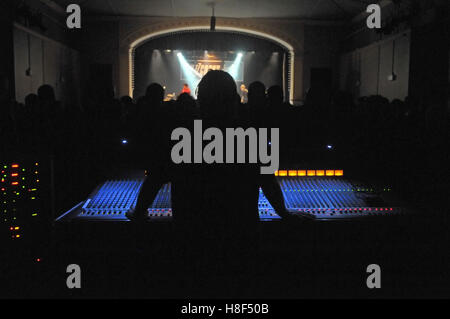 A sound engineer at his desk during a concert - Stock Photo
