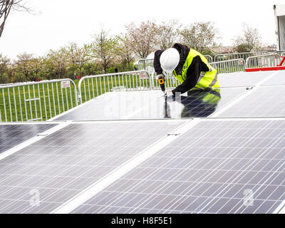 Workers install Solar Panels on Washington Mall with Washington Monument in background - Stock Photo