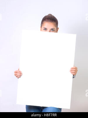 Banner sign woman peeking over edge of blank empty paper billboard with copy space for text - Stock Photo