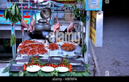 Marinated spicy meat and fish Pakistani food on display at street side restaurant Mall Road Murree Pakistan - Stock Photo