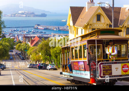 Brakeman appying cable car brakes going downhill on steep Hyde Street hill with sweeping view of Alcatraz Prison, - Stock Photo
