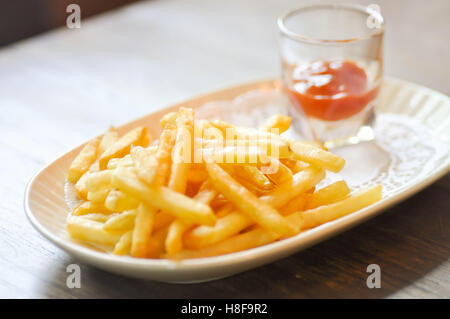 French fries dish and ketchup dip in soft focus - Stock Photo