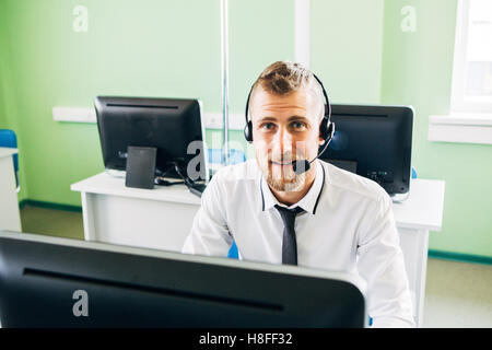 Businessman in the office on the phone with headset, looking camera - Stock Photo