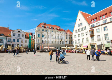 Tallinn, Estonia - May 2, 2016: Tourists and citizens walk on Town Hall square in old Tallinn, bright spring sunny - Stock Photo