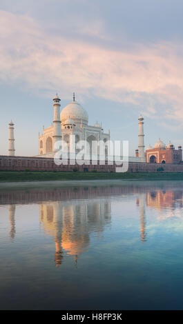 Majestic Taj Mahal marble glowing orange and red mosque beautifully reflected in the gentle Jamuna river on morning - Stock Photo