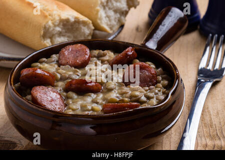 green lentil stew with sausage in brown bowl - Stock Photo