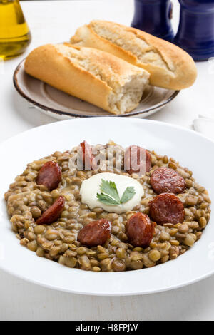 green lentil stew with sausage in white plate - Stock Photo