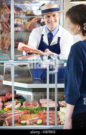 Butcher Serving Customer In Shop - Stock Photo