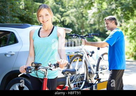 Mature Couple Taking Mountain Bikes From Rack On Car - Stock Photo