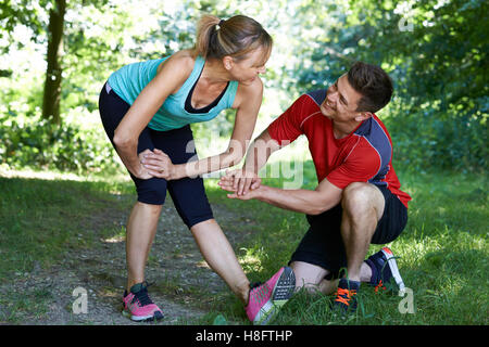 Mature Woman Exercising With Personal Trainer In Park - Stock Photo