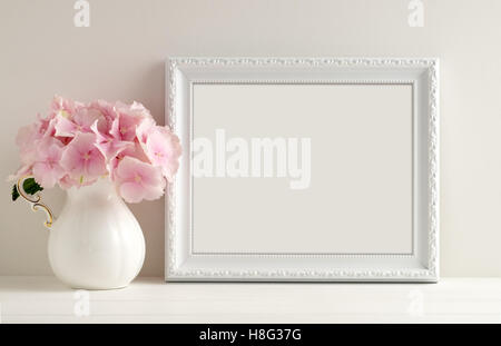 White landscape frame mockup with a vase of hydrangea beside the frame, overlay your quote, promotion, headline, - Stock Photo