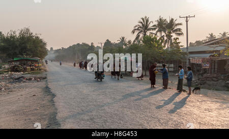 Road scene in rural Myanmar in early morning. Monks receiving alms from female villagers. Shwe Kyet Yet village, - Stock Photo