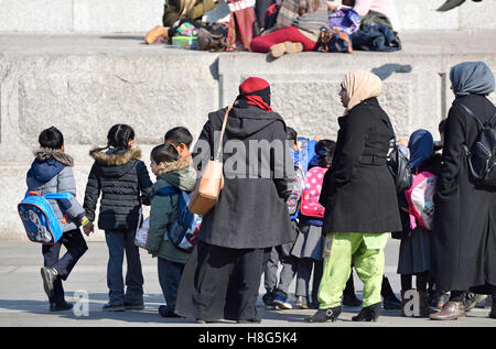London, England, UK. Muslim women and children on a school trip in Trafalgar Square - Stock Photo