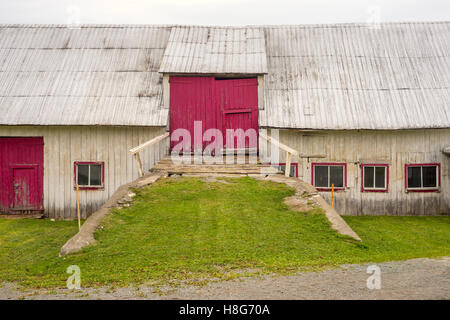 Facade of an old barn with red doors in Gaspe Peninsila, Quebec Province, Canada - Stock Photo