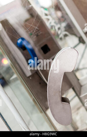 Closeup of door handle of slightly damaged Parisian phone booth with blue telephone in background and scratches - Stock Photo