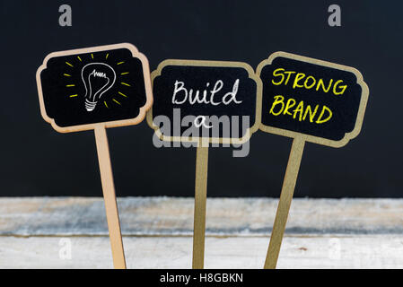 Concept message BUILD A STRONG BRAND and light bulb as symbol for idea written with chalk on wooden mini blackboard labels