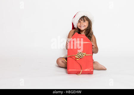 Smiling little girl in a Santa Claus hat is sitting and unpacking a Christmas gift on white background. - Stock Photo