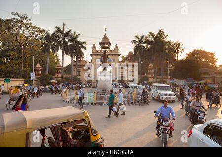 Traffic speeds around the roundabout at the BHU Main Gate and Malaviya statue in Varanasi, India - Stock Photo