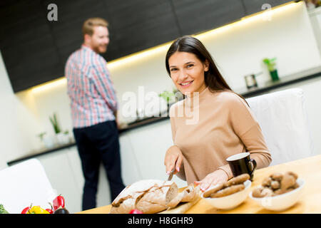 Young man washing dishes while the young woman cuts bread on table in modern kitchen - Stock Photo