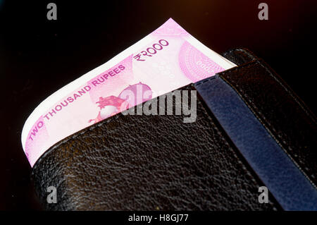 New Indian rupee 2000 note placed in a black leather wallet and isolated on black. The new currency has been introduced - Stock Photo