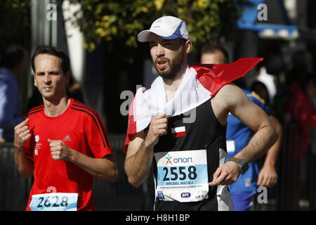 Athens, Greece. 13th November 2016. A runner is wrapped in a Polish flag. Thousands of people from all over the - Stock Photo