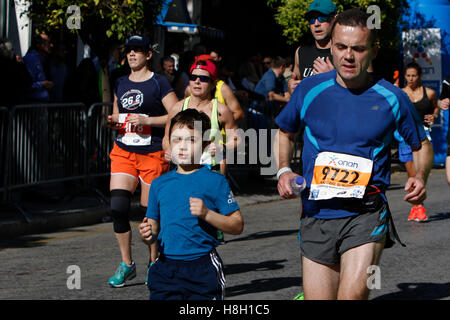 Athens, Greece. 13th November 2016. A father runs with his son in the Athens marathon. Thousands of people from - Stock Photo