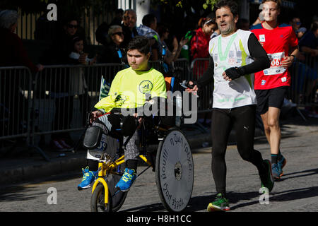 Athens, Greece. 13th November 2016. A runner pushes a boy in a wheel chair. Thousands of people from all over the - Stock Photo