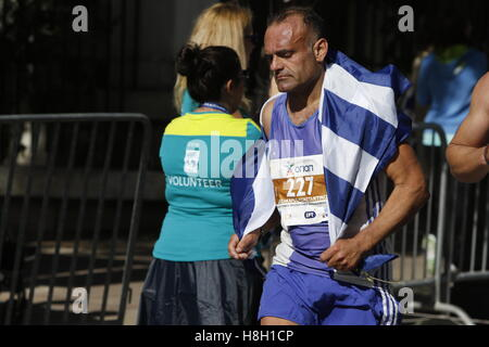 Athens, Greece. 13th November 2016. A runner is wrapped in a Greek flag. Thousands of people from all over the world - Stock Photo