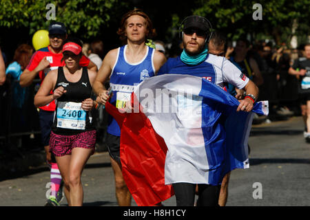 Athens, Greece. 13th November 2016. A runner carries a French flag. Thousands of people from all over the world - Stock Photo