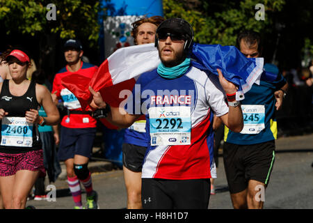 Athens, Greece. 13th November 2016. A runner is wrapped in a French flag. Thousands of people from all over the - Stock Photo