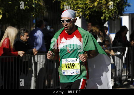 Athens, Greece. 13th November 2016. A runner is wrapped in an Italian flag. Thousands of people from all over the - Stock Photo