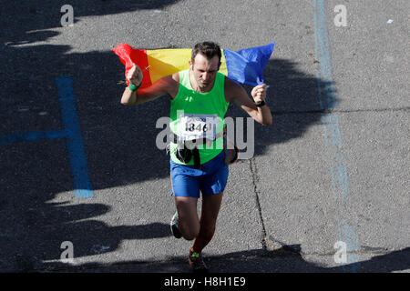 Athens, Greece. 13th November 2016. A runner carries a Romanian flag. Thousands of people from all over the world - Stock Photo