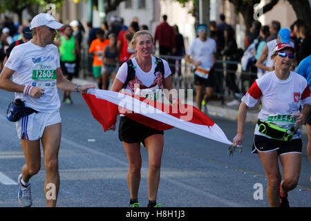 Athens, Greece. 13th November 2016. Three Polish runners carry a Polish flag. Thousands of people from all over - Stock Photo