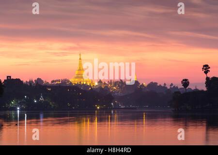 Shwedagon pagoda at sunset, as seen from Kandawgyi lake, Yangon, Myanmar - Stock Photo