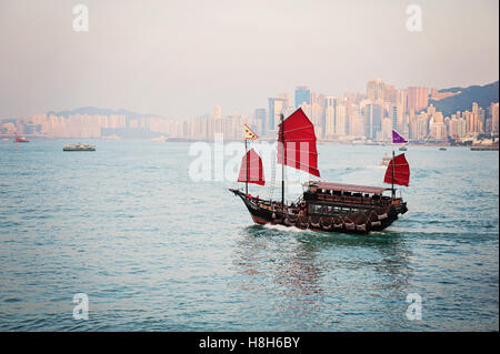 Traditional Chinese junk boat with red sails in Hong Kong's Victoria Harbour at dusk - Stock Photo