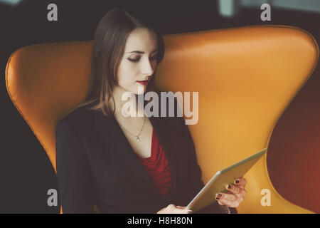 Portrait of young successful woman entrepreneur in a red dress and jacket sitting on orange armchair and working - Stock Photo
