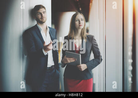 Group of business people: man in formal suit and woman in red dress and jacket holding tablet, man is showing something - Stock Photo