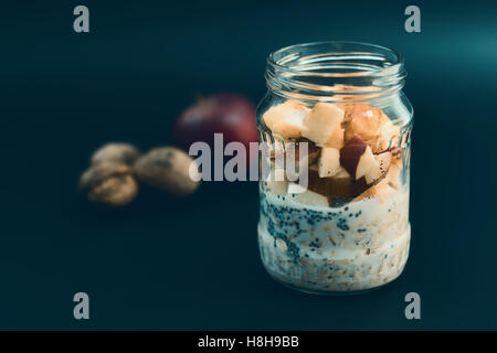 Healthy breakfast with chia seeds. Apple nut overnight oats and chia, in glass jar. Preparation overnight breakfast - Stock Photo