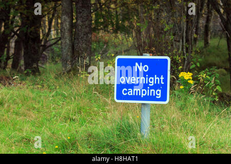 Blue No Overnight Camping sign on a short post by the side of the road - Stock Photo
