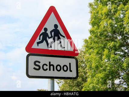 Red and White Triangular School sign with trees and sky background - Stock Photo
